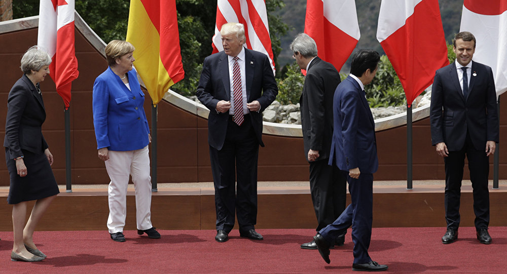 U.S. President Donald Trump, center, stands with other G7 leaders as they prepare for a group photo during the G7 Summit in the Ancient Theatre of Taormina ( 3rd century BC) in the Sicilian citadel of Taormina, Italy, Friday, May 26, 2017