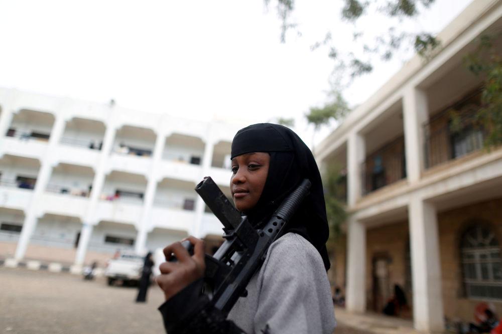Una ragazza con un fucile giocattolo spostata per i combattimenti nella città di Hodeidah a Yemen.