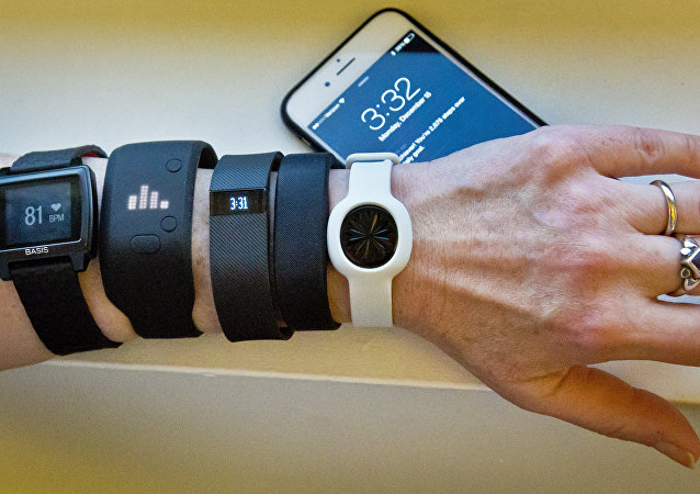 Fitness trackers, from left, Basis Peak, Adidas Fit Smart, Fitbit Charge, Sony SmartBand, and Jawbone Move, are posed for a photo next to an iPhone, in New York (File)