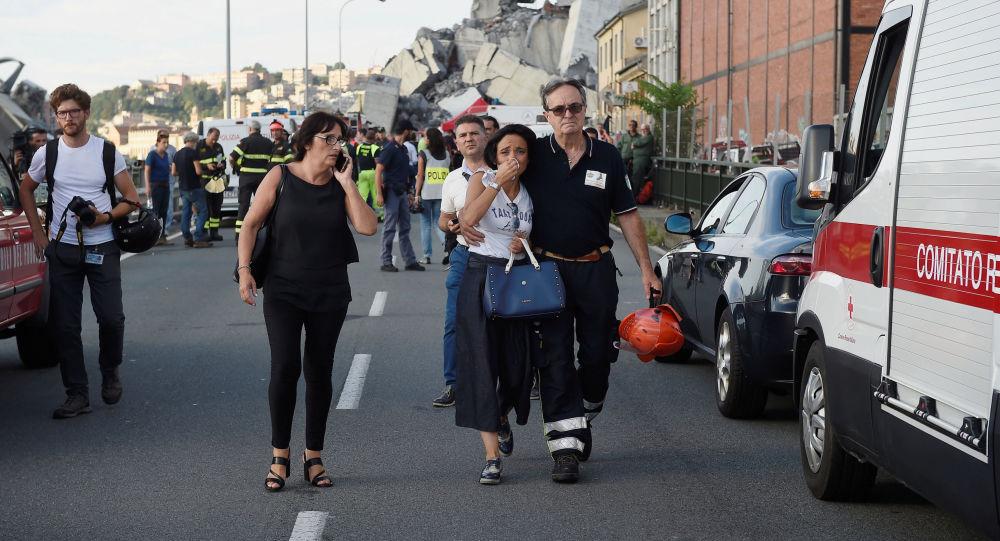 Un vigile di fuoco accompagna una donna al sito del crollo del ponte Morandi a Genova