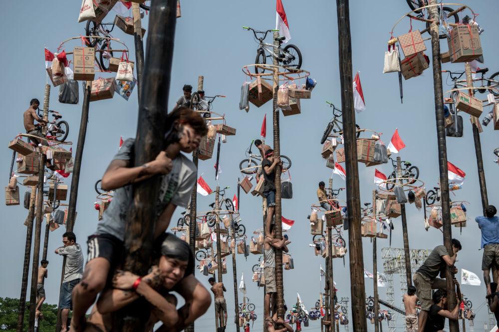 I partecipanti al concorso Panjat Pinang a Jakarta per i Giochi asiatici 2018