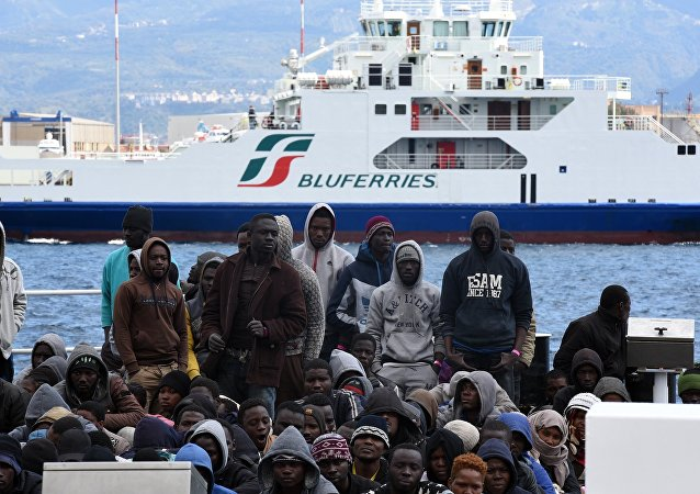Migrants and refugees wait to disembark in the port of Messina following a rescue operation at sea by the Italian Coast Guard ship Diciotti on March 17, 2016 in Sicily.