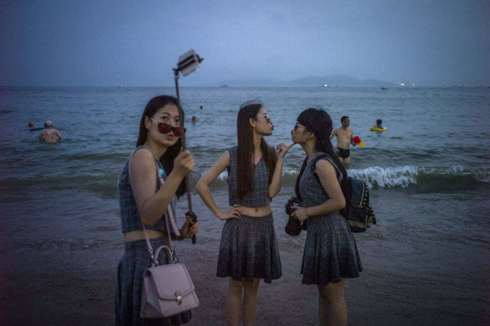 Ragazze cinesi si fotografano sulla spiaggia della città di Xindao
