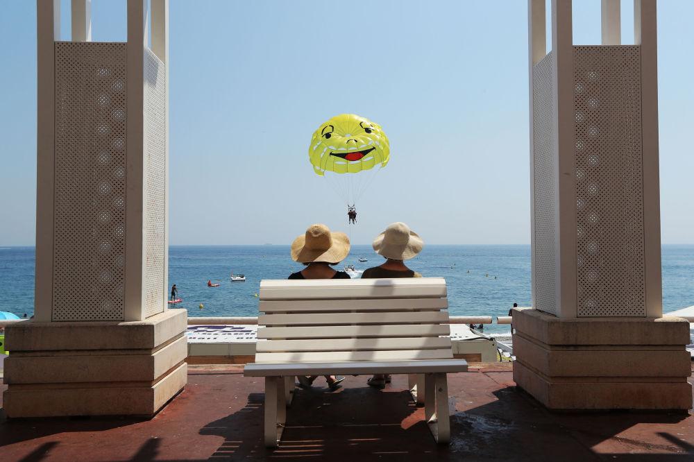 Spettatori osservano paracadutista ascensionale a Nizza, Francia