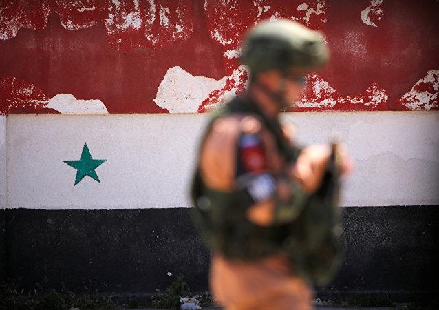 Un soldato russo sta di fronte alla bandiera nazionale siriana