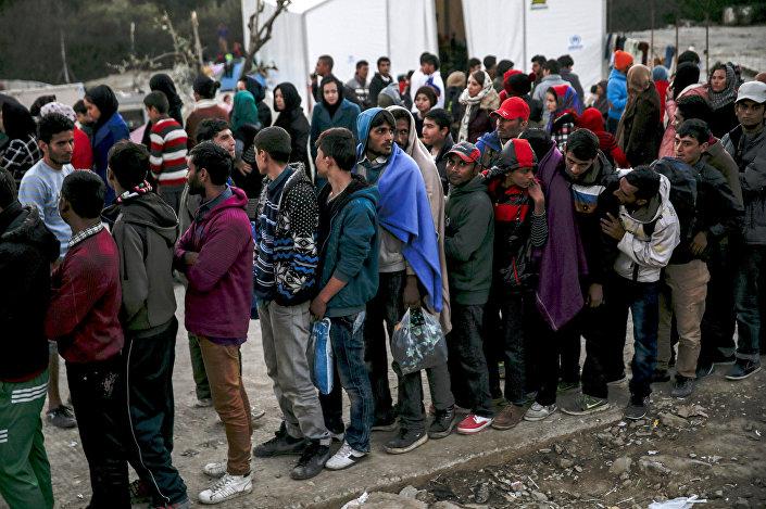 Rifugiati e migranti fanno la cosa per la distribuzione del cibo al campo di Moria sull'isola greca di Lesbo