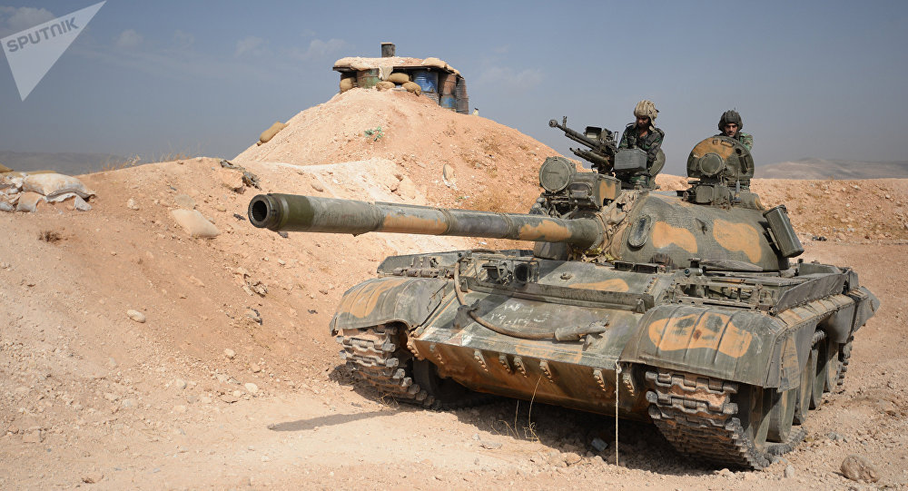 The crew of a T-72 tank of the 10th Division, 2nd Corps of the Syrian Arab Army are on combat alert off Katana, Damascus Province