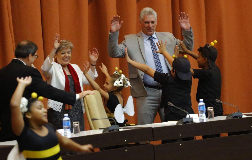 Il Presidente cubano Mighel Diaz-Canel balla con gli attori del teatro giovanile durante l'apertura della conferenza economica a L'Havana