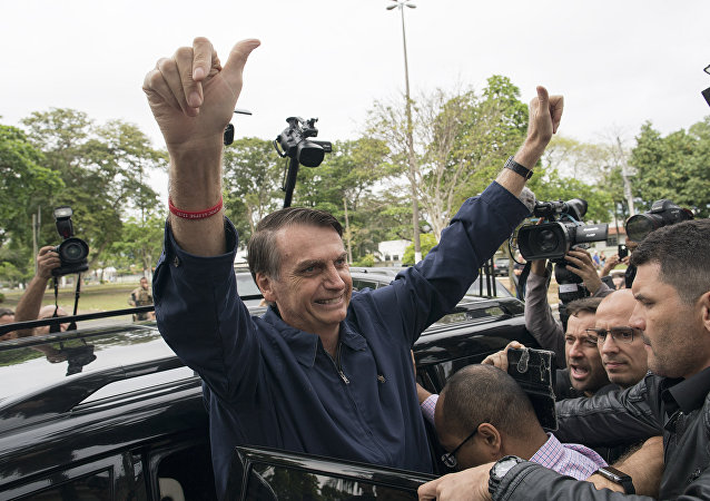 Presidential frontrunner Jair Bolsonaro, of the Social Liberal Party, flashes thumbs up to supporters after voting at a polling station in Rio de Janeiro, Brazil, Sunday, Oct. 7, 2018.