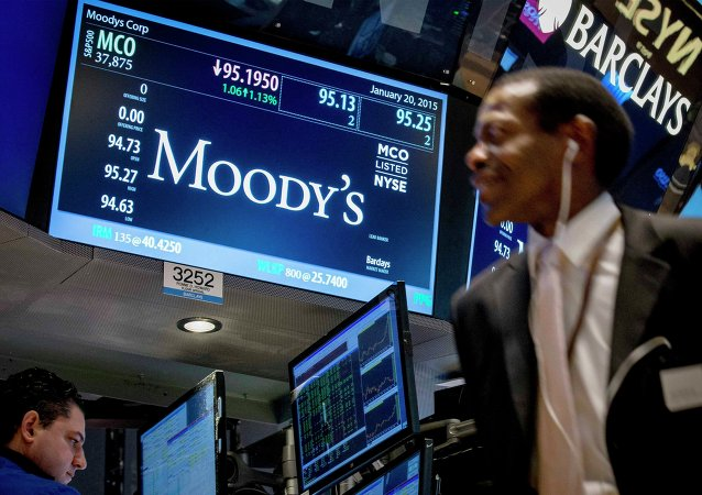 A screen displays Moody's ticker information as traders work on the floor of the New York Stock Exchange January 20, 2015