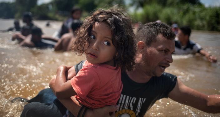 Migranti dall'Honduras attraversano a piedi il fiume Suchiate al confine con il Messico, durante il loro viaggio verso gli USA.