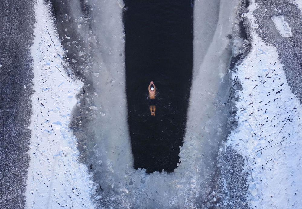 Una persona nuota nel lago parzialmente ghiacciato in Cina