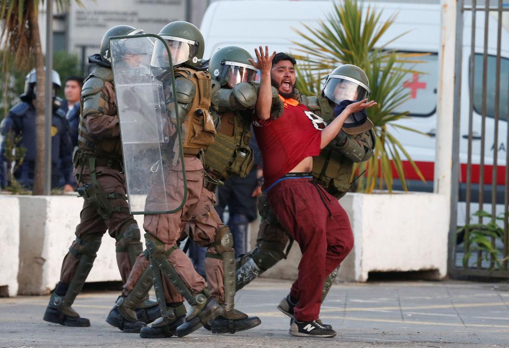 Scaricatore di porto, fermato dalla polizia durante le proteste a Valparaiso, Cile.