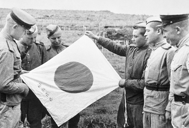 I militari sovietici con una bandiera giapponese abbandonata