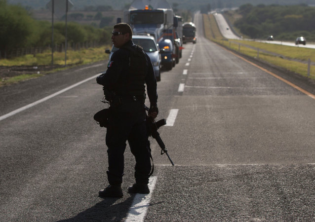 Mexican state police stop traffic, near the entrance of Rancho del Sol, near Ecuanduero, in western Mexico, Friday, May 22, 2015