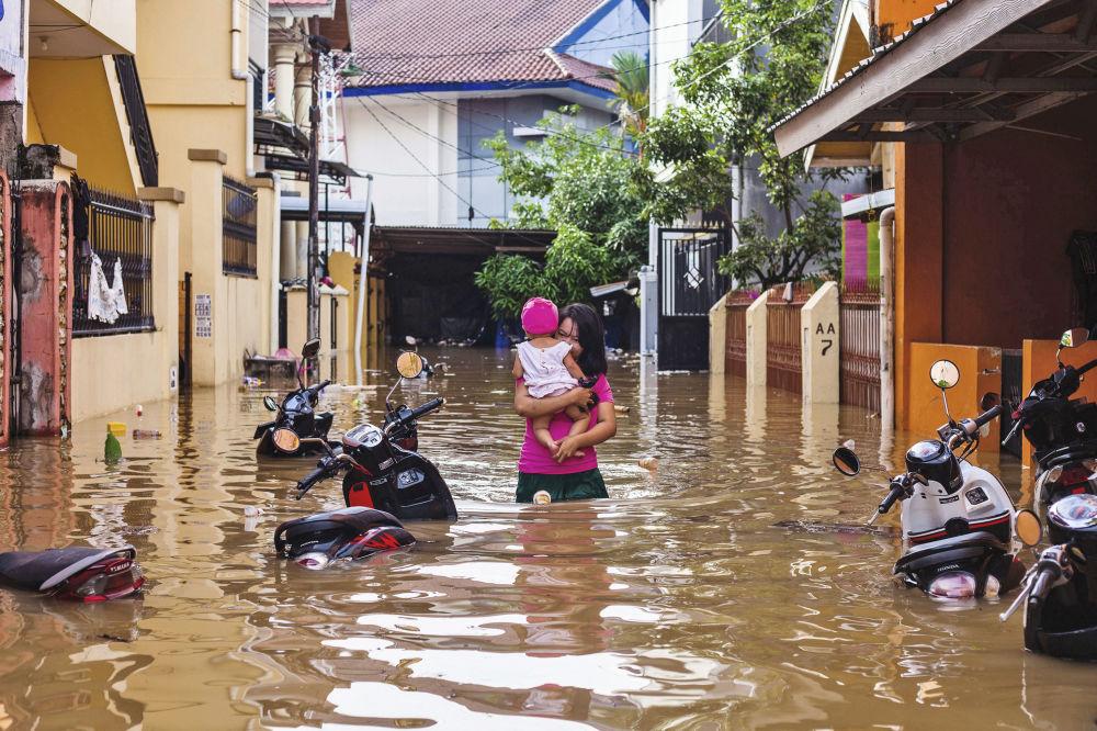 Una donna sta portando un bambino in una via inondata in una città indonesiana Makassar.