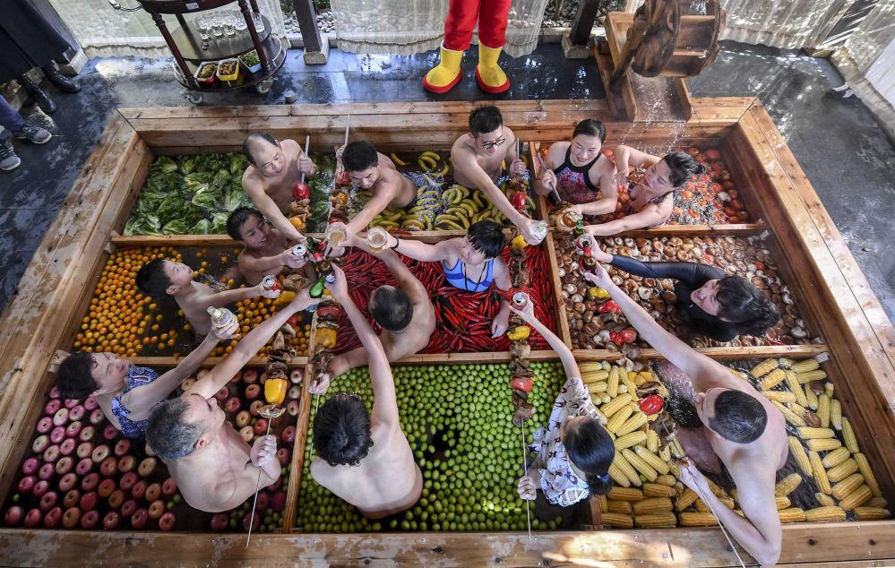 Gli ospiti di un albergo a Hangzhou passano il tempo nella piscina riempita di frutta e verdura alla vigiglia del Capodanno cinese.