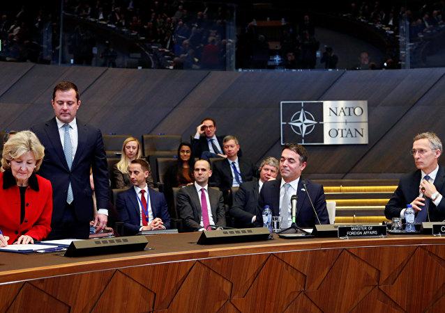 L'ambasciatore statunitense in NATO Kay Bailey Hutchison, il ministro degli Esteri macedone Nikola Dimitrov e il segretario generale della NATO Jens Stoltenberg alla firma del protocollo di adesione della Macedonia alla NATO, Bruxelles, Belgio.
