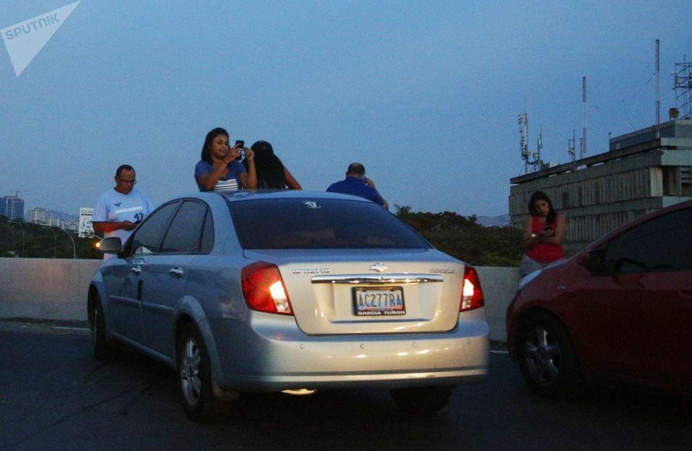 Abitanti di Caracas sull'autostrada cercano di ricevere il segnale dei cellulari