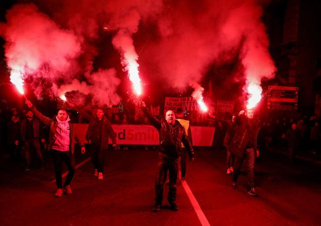 I dimostranti accendono bengala durante una protesta contro il presidente serbo Aleksandar Vucic e il suo governo nel centro di Belgrado, in Serbia, il 16 febbraio 2019.