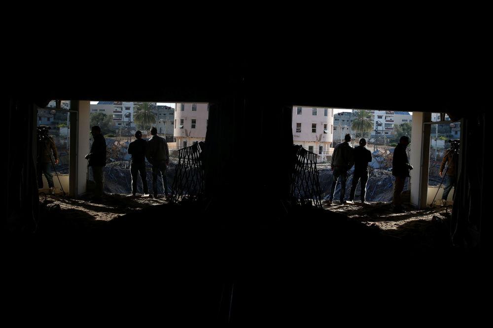 Palestinesi al di fuori dell'ufficio del leader di Hamas, Ismail Haniyeh, dopo i bombardamenti israeliani