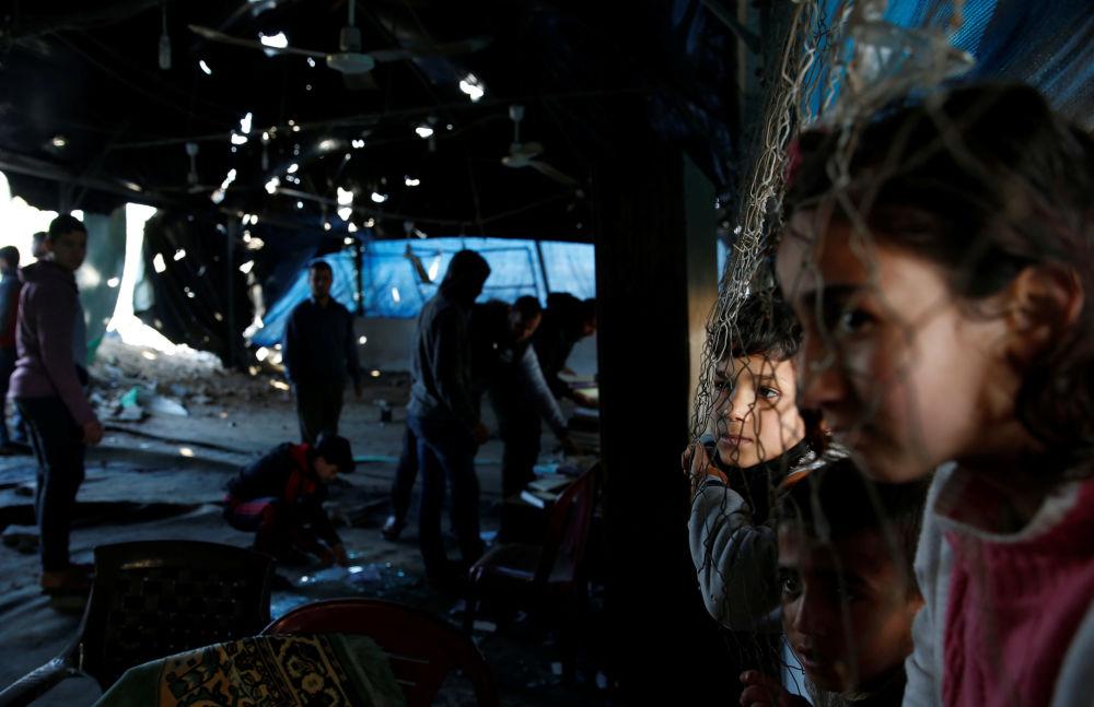 Bambini palestinesi osservano i resti di un edificio bombardato