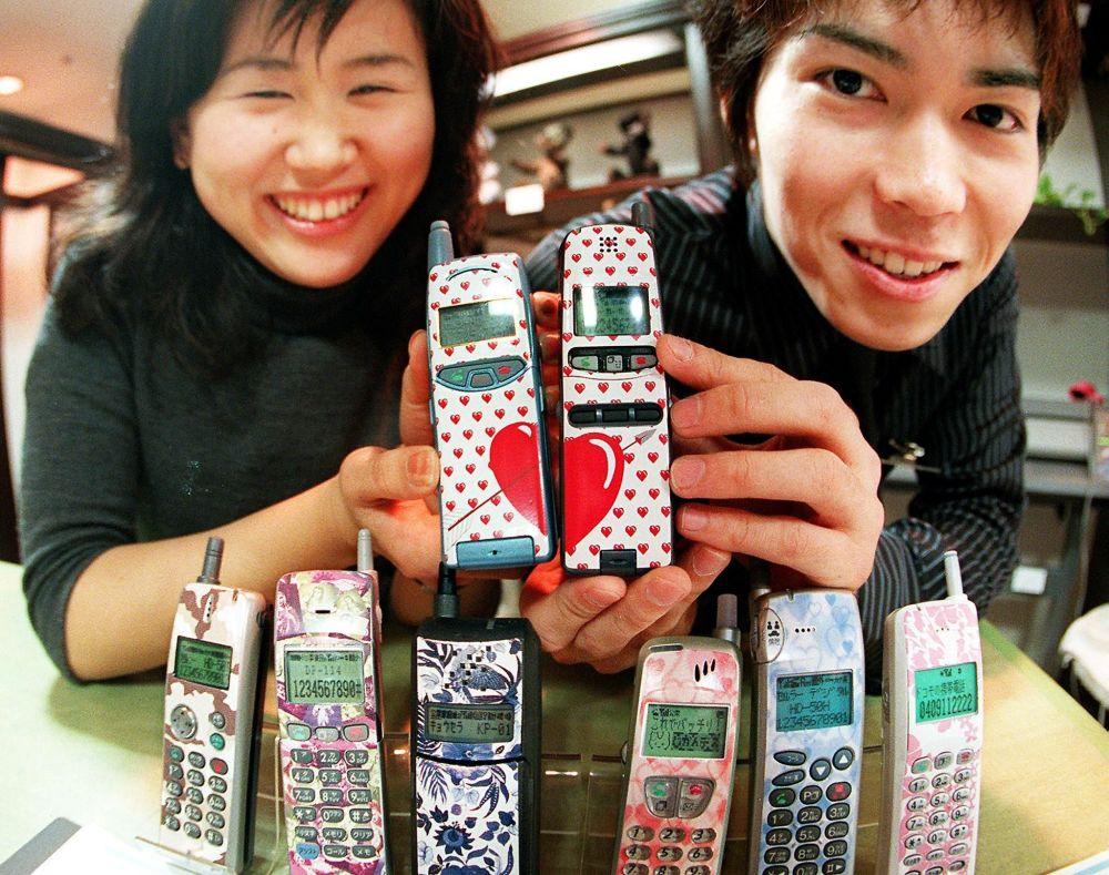 Tokyo, 10 marzo 1999 - una coppia di giovani innamorati giapponesi fotografata con i rispettivi cellulari ricoperti da una cover a tema