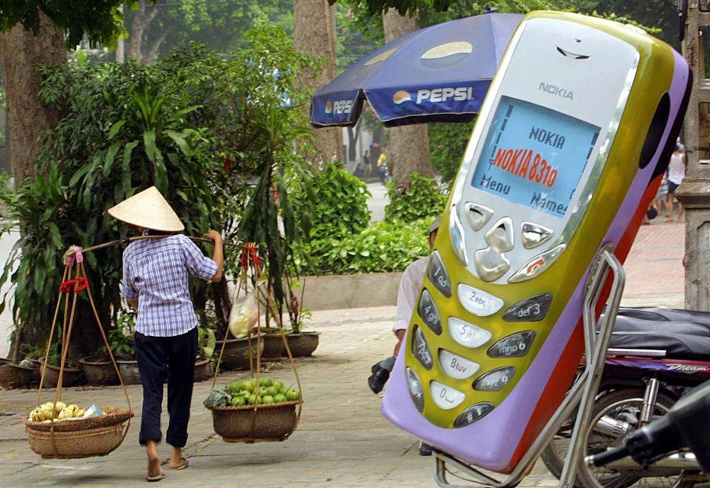 Hanoi, 2002 - Una venditrice di frutta passa accanto ad una riproduzione gigante di un telefonino Nokia 8310