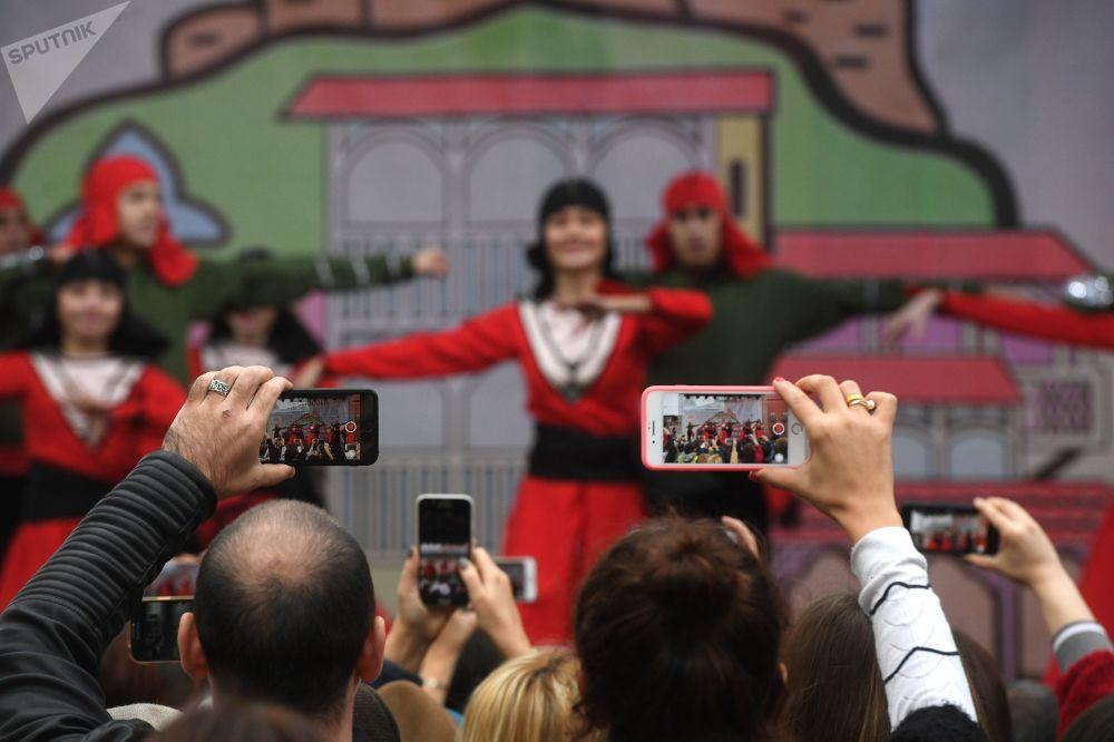 Tbilisi, 2018: spettatori filmano con i propri telefonini l'esibizione di un gruppo folcloristico in occasione del festival culturale Tbilisoba
