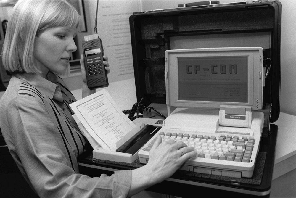 Hannover, CeBit, 1990 - Una ragazza tasta il modellino di un ufficio portatile, contenente un notebook, una stampante ed un telefono portatile.
