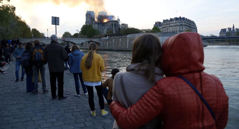 La gente sta guardando bruciare la cattedrale di Notre-Dame