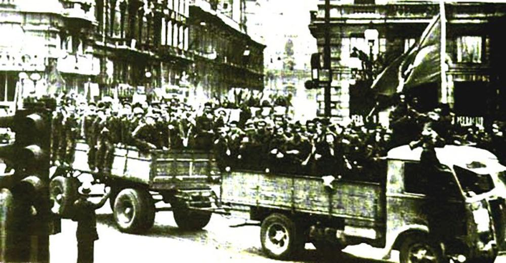 Partigiani sfilano su degli automezzi per le strade di Bologna liberata il 21 aprile 1945