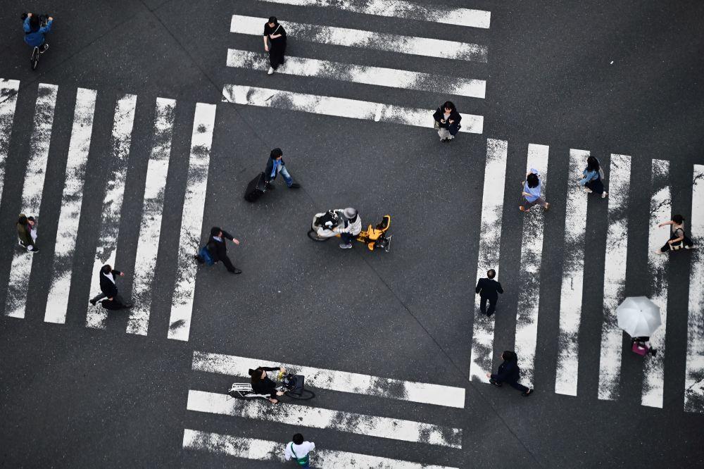 Pedoni attraversano la strada a Tokyo, Giappone.