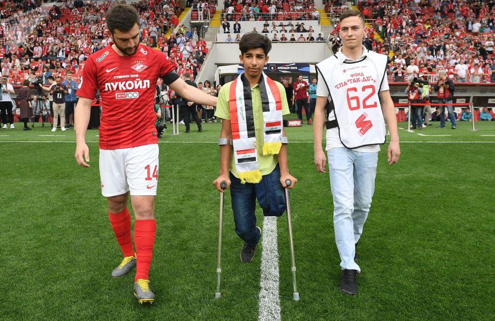 Il capitano dello Spartak Mosca Georgiy Dzhikia accompagna Qasim al centro del campo dello stadio Otkrytie Arena di Mosca, dove il ragazzino iracheno darà il calcio d'inizio della partita Spartak-Ufa