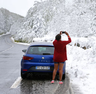 Una turista fotografa la neve fuori stagione in Corsica