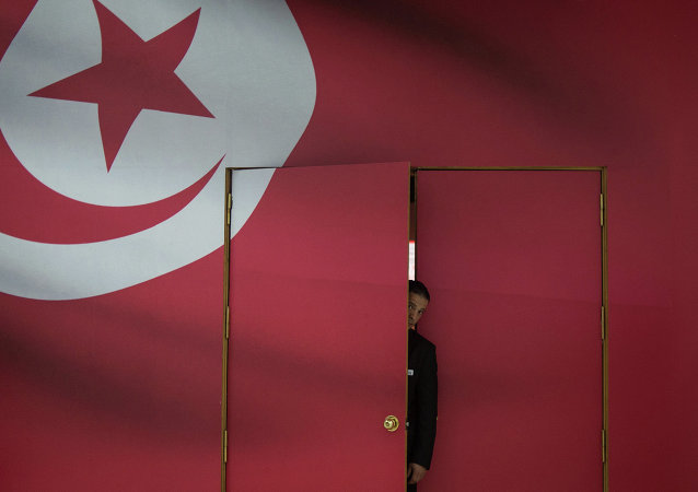 A Tunisian guard looks out of the main gate of media center for its parliamentary election in Tunis, capital of Tunisia, on Oct. 25, 2014