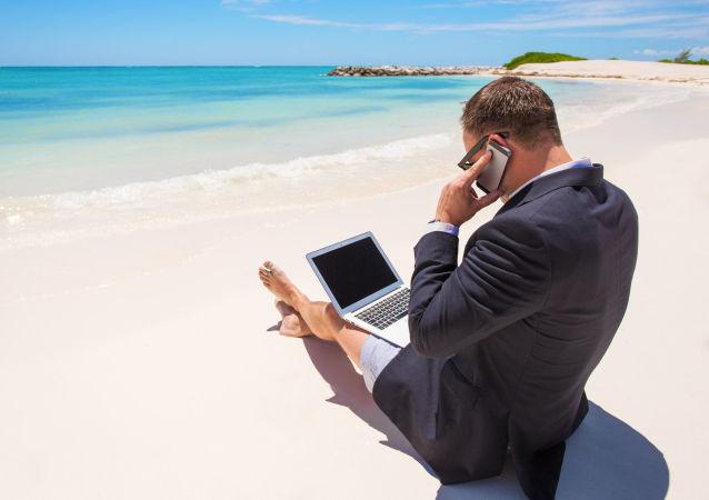 Uomo lavora al computer e telefono in spiaggia