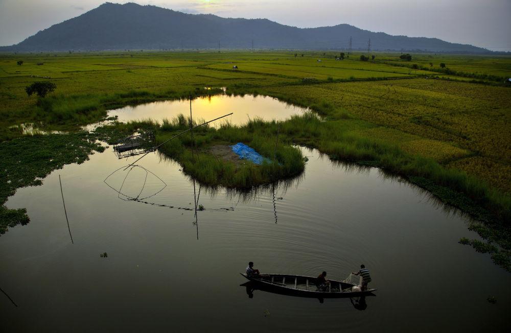 Pescatori su una barca di legno nel fiume Brahmaputra in India