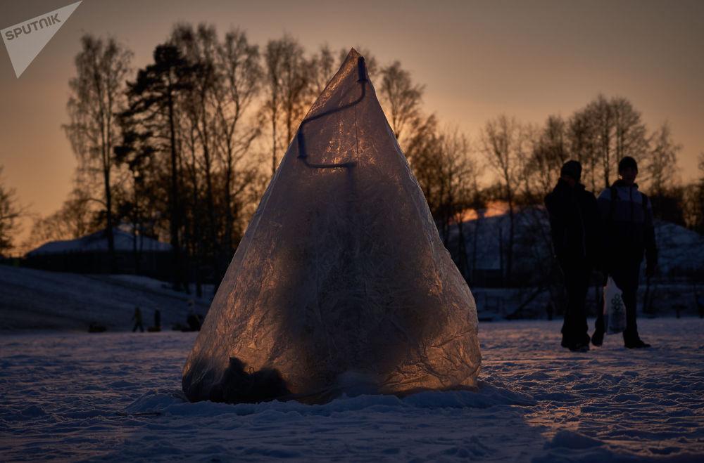 Un pescatore nel suo rifugio di cellophane in un lago vicino a San Pietroburgo d'inverno