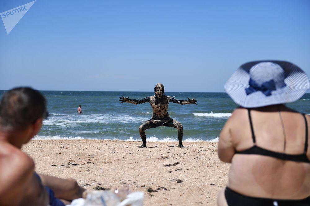 Un turista spaventa i bagnanti sulla spiaggia del mare di Azov separata dal lago Chokrak soltanto da una lingua di terra larga poche decine di metri. Dopo i bagni nel fango è di prassi tuffarsi nel mare per sciacquare il corpo.