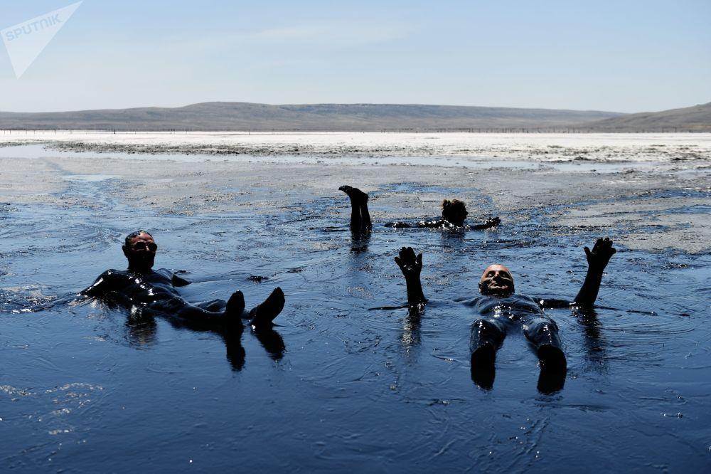 Turisti sporchi e felici nelle acque del lago Chokrak, in Crimea