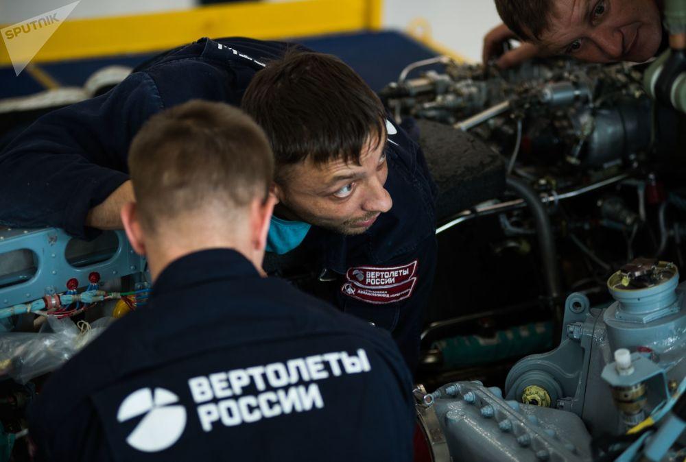 Due operai impegnati nel montaggio del motore di un elicottero Ka-52