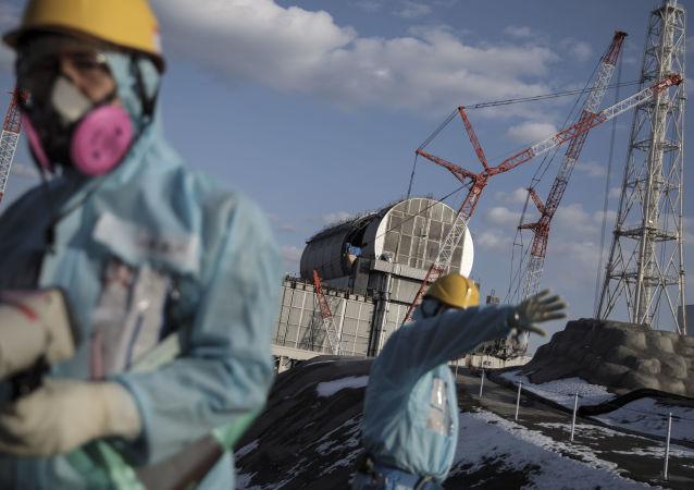 Operai di fronte alla centrale elettrica nucleare di Fukushima, Giappone