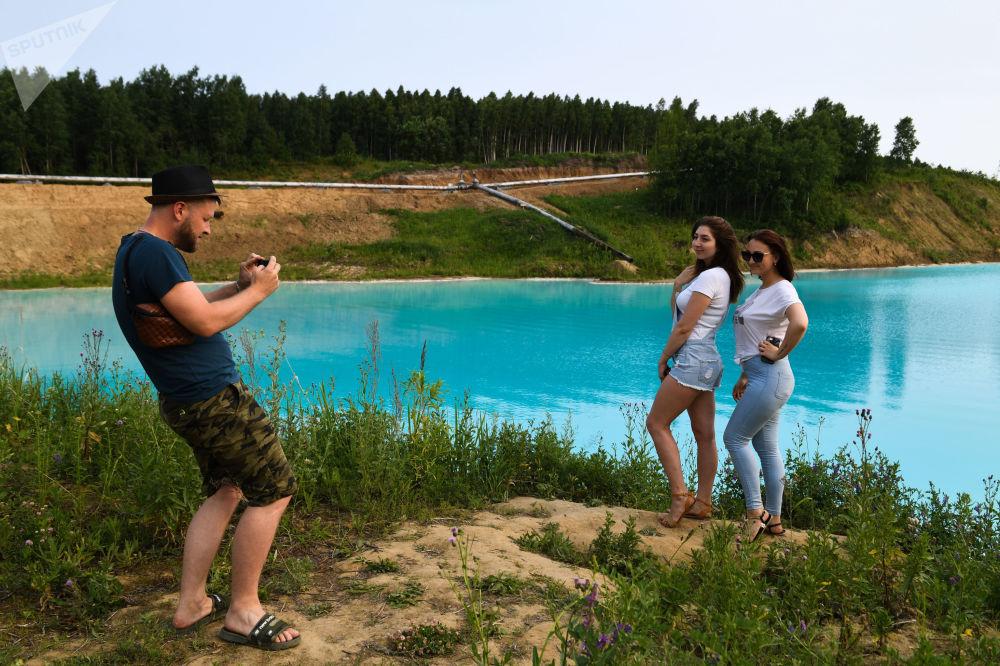 Le ragazze si fanno una foto vicino alla centrale termoelettrica di Novosibirsk diventata popolare tra  gli amanti dei selfie straordinari per il colore dell'acqua.