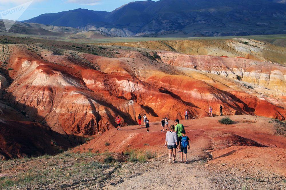 Turisti in cammino lungo la strada che conduce alla valle rossa di Kyzyl-Chin: per raggiungerla dal villaggio più vicino, Ortolyk, bisogna percorrere 21 km (gli ultimi 7 dei quali sterrati)