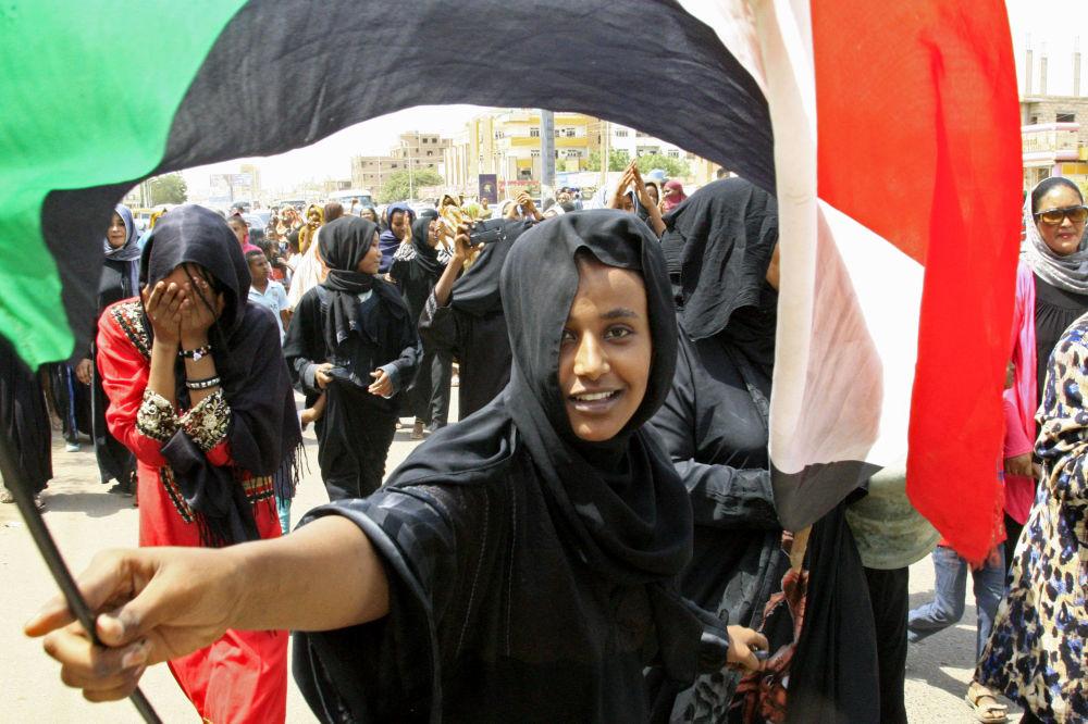 Una giovane sudanese sventola la bandiera del suo paese in segno di gioia per la firma dell'accordo tra il Consiglio dei militari ed il Fronte nazionale di liberazione del paese, dopo sette mesi di violenti scontri
