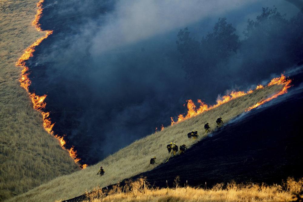 Pompieri al lavoro per spegnere le fiamme vicino alla città di Brentwood in California