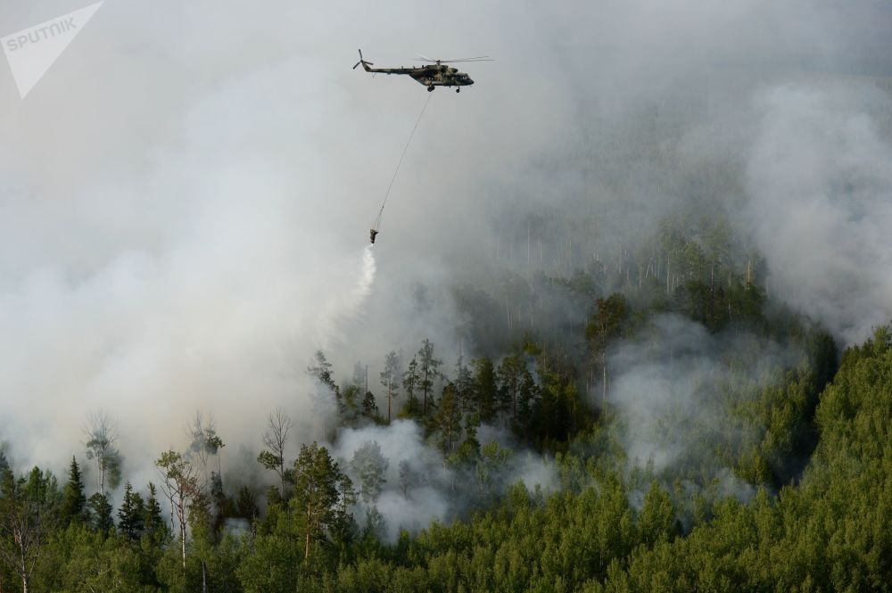 Un elicottero Mil Mi-8 dei vigili del fuoco russi in volo sopra i boschi in fiamme della regione di Krasnoyarsk, in Siberia