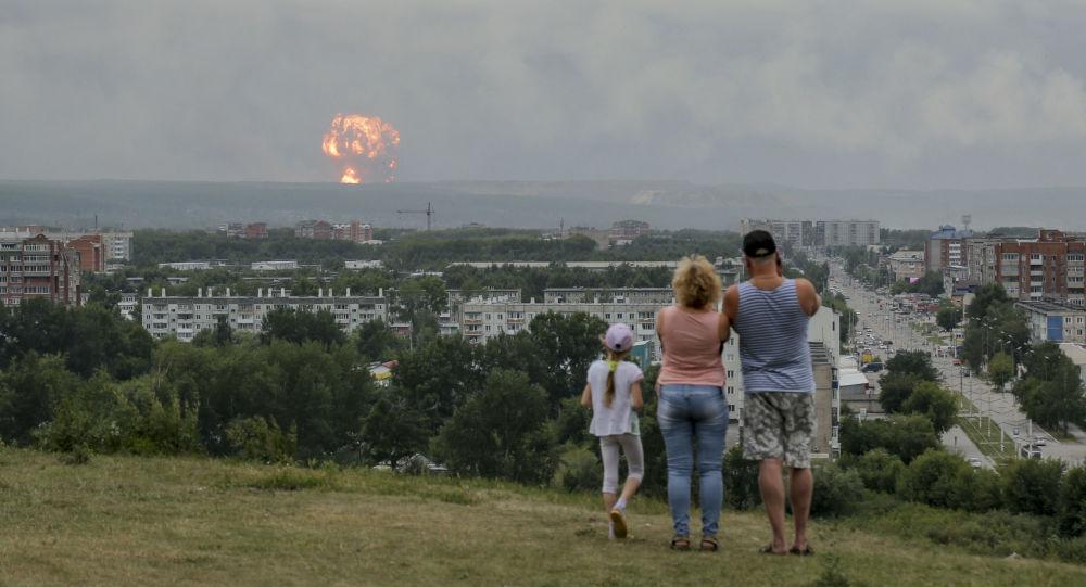 Agosto 5, 2019, una famiglia guarda l'esplosione in un deposito di munizioni vicino alla città russa di Achinsk