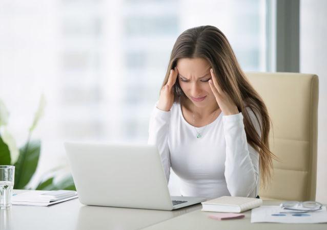 Ragazza con mal di testa davanti al computer